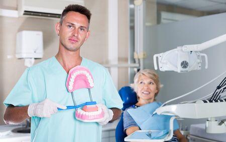 Professional dentist man explaining correct tooth brushing on dental model Stock Photo