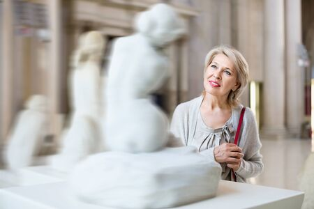 Adult cheerful positive female looking at artwork sculpture in the museum indoors Banque d'images