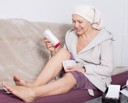 Elderly woman performing body hair removal at home