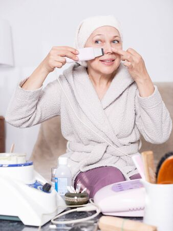 Elderly woman performing ultrasonic face cleaning with device at home