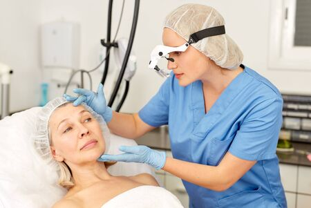 Doctor is examining mature woman patient before the procedure