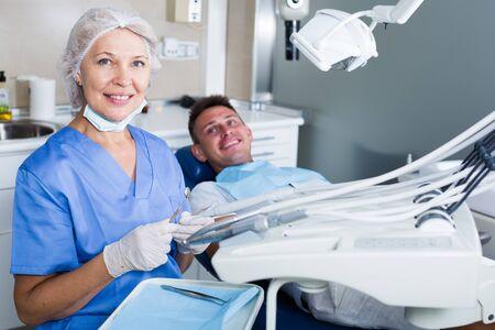 Porträt des professionellen Zahnarztes in der Zahnklinik mit dem Patienten dahinter