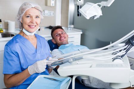 Portrait of professional dentist in dental clinic with patient behind