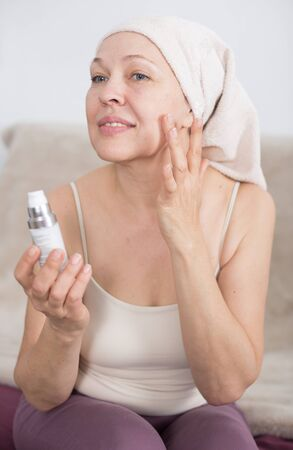 Senior woman putting cream on face during beauty procedures at home