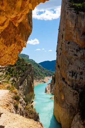 Unique landscape of Mont-Rebei Gorge and Noguera Ribagorçana River between steep rocky cliffs covered with greenery, Spain