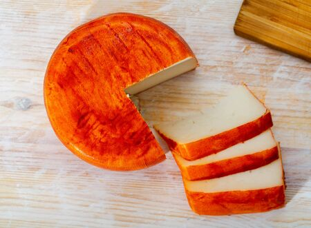 Head of ripened goat cheese with paprika on wooden table Foto de archivo