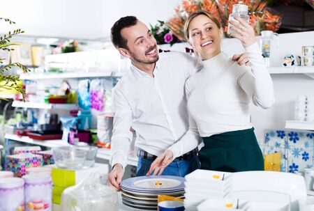 Young cheerful couple deciding on best crockery in dinnerware store