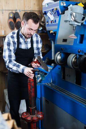 Adult male worker repairing shoe in specialized workshop Stockfoto