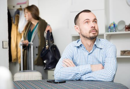 Frustrated man sitting at table on background with young woman leaving his apartment with suitcase
