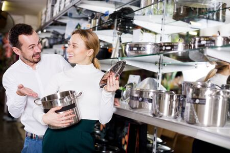 Young couple examining various saucepans in dinnerware store