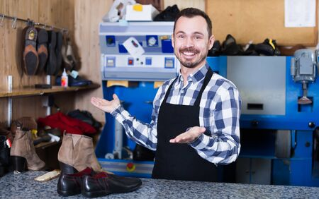 Ordinary man worker displaying his workplace and tools in shoe repair workshop