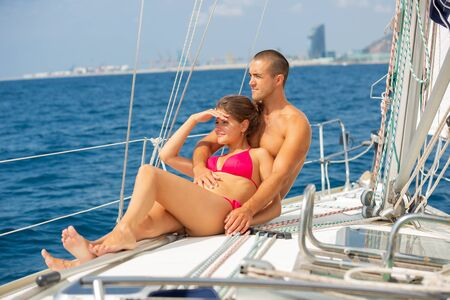 Portrait happy couple sailing on yacht in calm blue sea along Spanish coast during romantic summer vacation