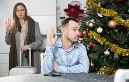 Man upset because of his wife leaving on  business trip on Christmas holidays Фото со стока