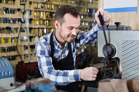 Young diligent friendly male worker making key in specialized workshop Stockfoto