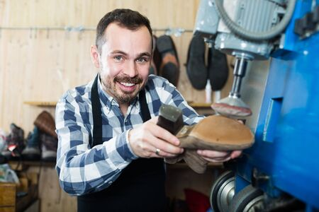 Smiling russian male worker fixing failed shoes in shoe repair workshop