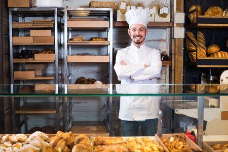 Panadero sonriente en el trabajo en la panadería Foto de archivo