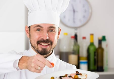 Smiling man cook making tasty dishes in kitchen Imagens