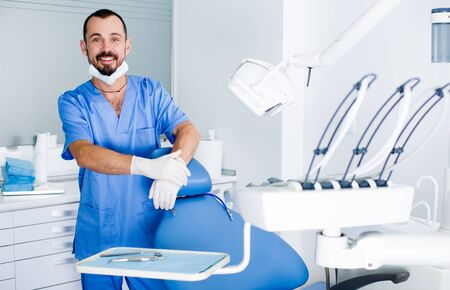 male Dentist is ready to accept client in clinic Stock Photo