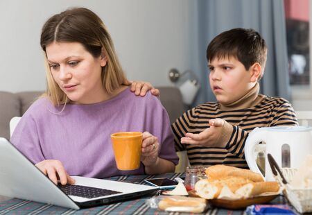 Young woman working at laptop and son trying to talking with she indoors