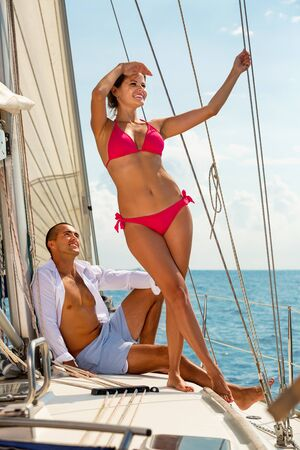 Young attractive pleasant cheerful smiling woman enjoying sea trip with boyfriend on deck of their sailboat on sunny summer day