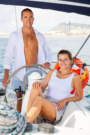 Confident man standing at wheel of his yacht during sea vacation with attractive woman