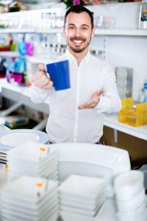 Young happy  man choosing new mug in dinnerware store