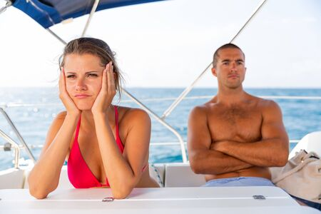 Portrait of offended young woman after quarrel with husband during sea trip on sailboat