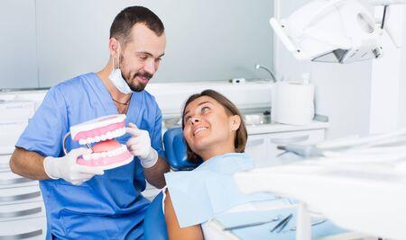 Joven médico en uniforme dice sobre la higiene de los dientes en el consultorio dental Foto de archivo