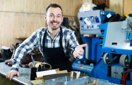 Laughing man worker displaying his workplace and tools in shoe repair workshop