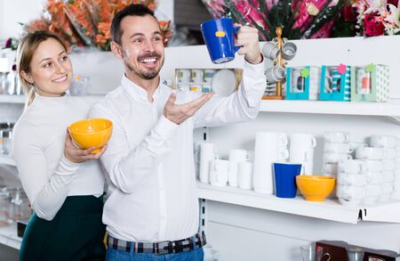 Adult guy and girl deciding on practical cup in dinnerware store Stok Fotoğraf