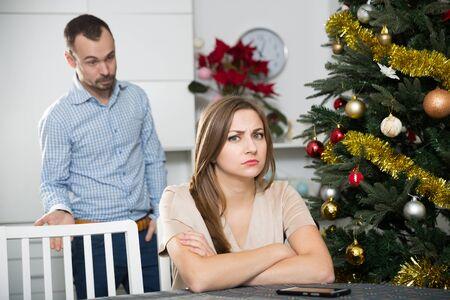 Young couple quarreling during Christmas celebration Фото со стока