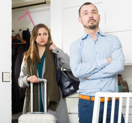 Unhappy couple quarreling because of business trip of wife Stock Photo