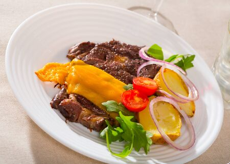 Well-cooked beef steak with cheese and baked potatoes served at plate with tomatoes Stock Photo