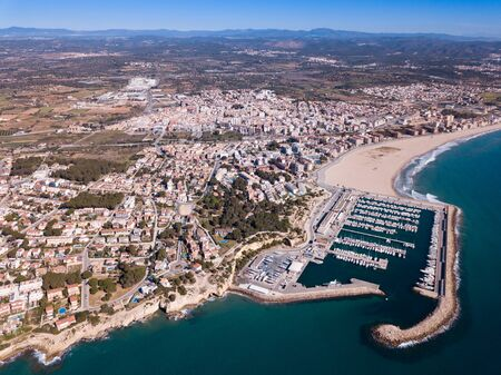 Picturesque aerial view of Mediterranean coastal town of Torredembarra with yachts moored in harbor, Tarragona, Spain