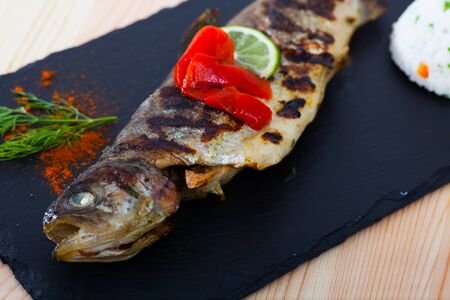 Image of  tasty baked whole trout  with rice, served with lemon and greens at plate