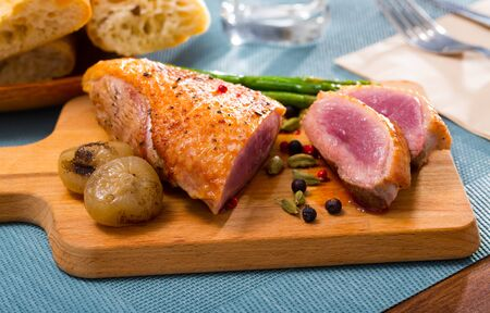 Duck breast with baked onions and asparagus Фото со стока