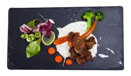 Top view  of tasty chicken heart with cream sauce served with vegetables at plate. Isolated over white background