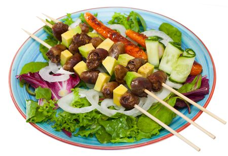 Fried shish-kebab from chicken hearts with  avocado and  fresh lettuce served at plate. Isolated over white background   Stock Photo