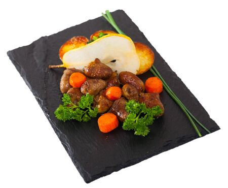 Top view  of tasty chicken hearts with  baked vegetables and fresh pear at plate. Isolated over white background