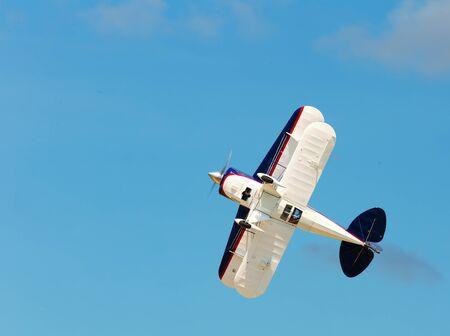 Light biplane demonstrating flying capabilities in sunny sky