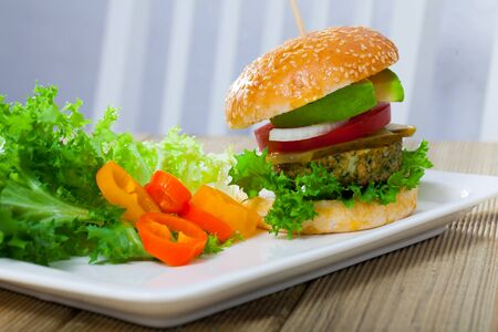 Delicious falafel burger with lettuce, tomato, onion, pickled cucumbers and avocado served on plate with vegetables
