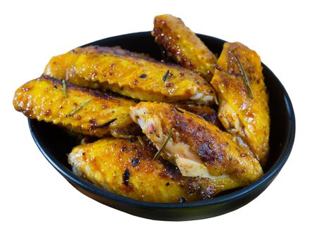 Black bowl of appetizing roasted chicken wings with two kinds of sauce. Isolated over white background