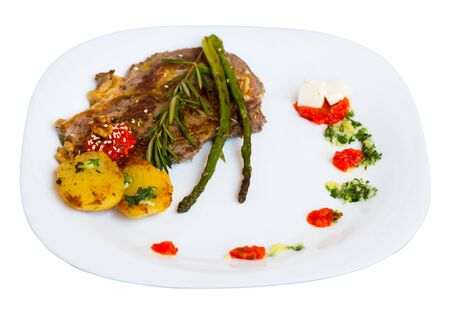 Roasted veal steak served with baked vegetables, adjika and garlic herbs sauce. Isolated over white background