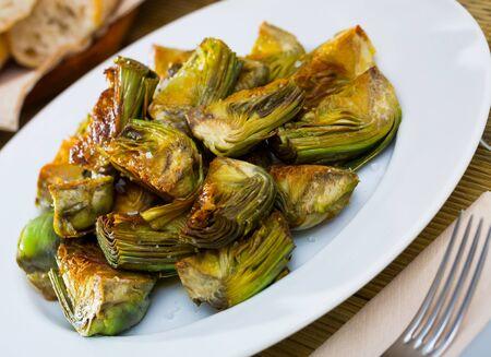 Delicious fried artichoke halves on a white plate