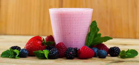 Healthy vitamin milkshake with mix of ripe berries and mint leaves served in glass Stock Photo