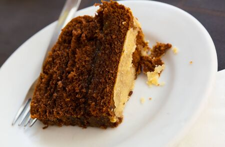 Portion of delicious chocolate orange cake on white plate