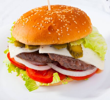 Image of double cheeseburger with beef, tomato, cheese, cucumber and lettuce Stock Photo