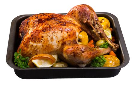 Tasty turkey baked with vegetables and apples, served with lemon slices and greens in baking dish. Isolated over white background Stock Photo