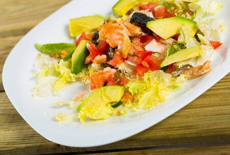 Fresh colorful salad with grilled salmon, ripe avocado, tomatoes, lettuce leaves and lemon