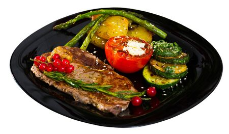 Appetizing grilled veal loin with baked vegetables served with redcurrant on ceramic plate. Isolated over white background
